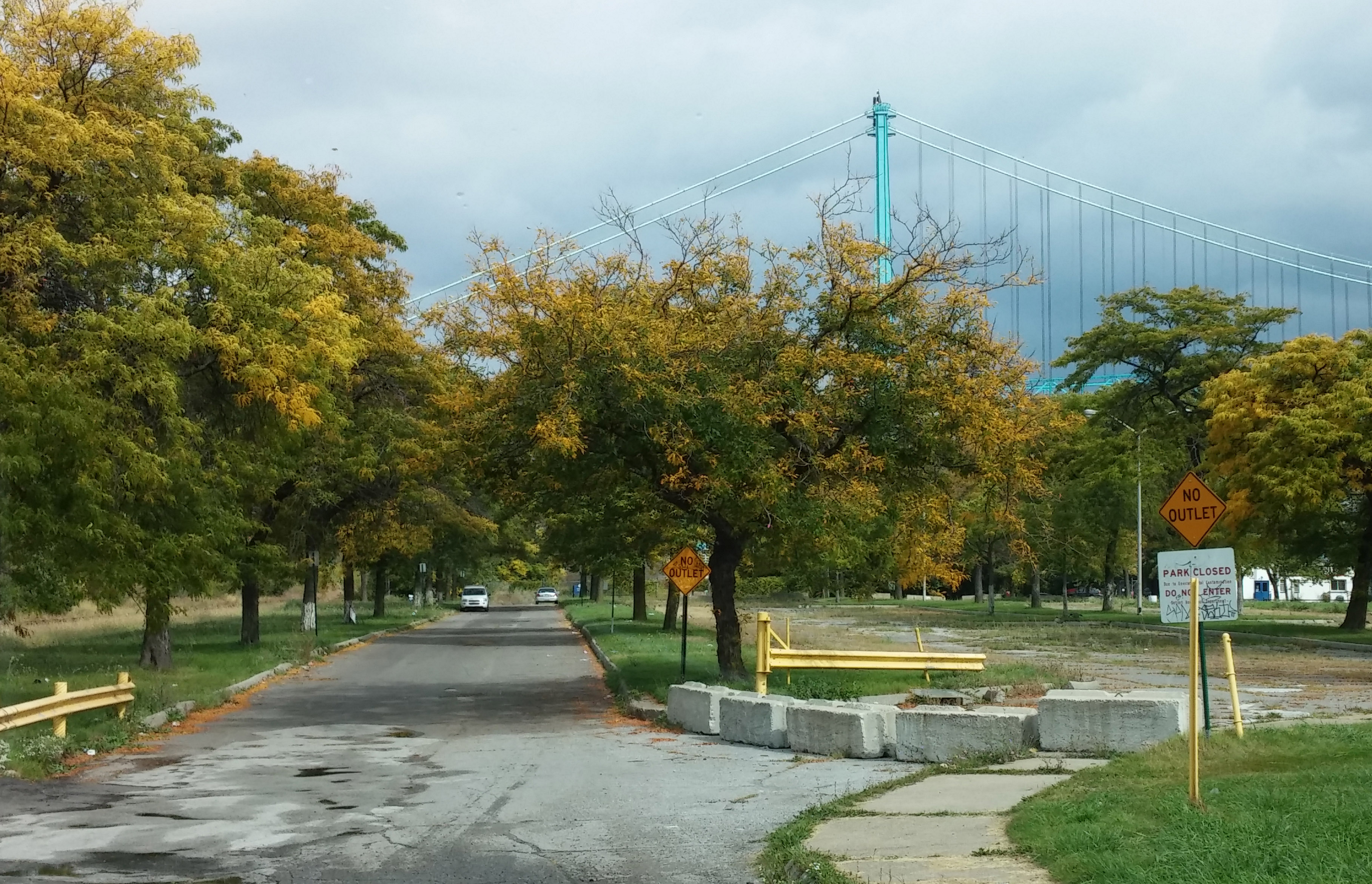 View of the Ambassador Bridge from the roadside adjacent to Riverside Park. The park is currently closed due to environmental contamination.